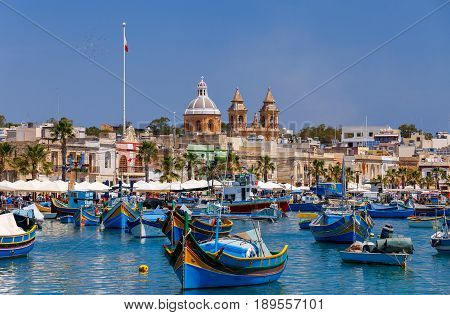 Traditional multicolored fishing boats Luzzi in the harbor Marsaxlokk. Malta.