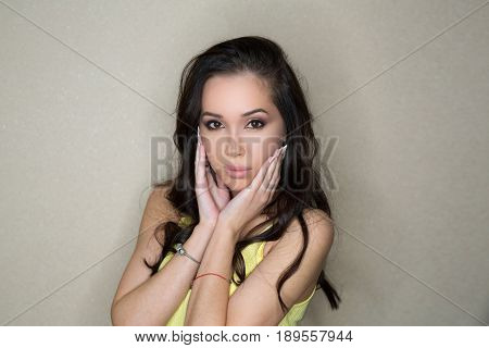 Beautiful young slender girl with dark hair in studio on wall background
