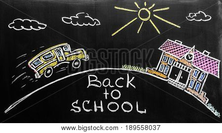 Back to school background with school bus and school are written by colorful chalks on the black school chalkboard