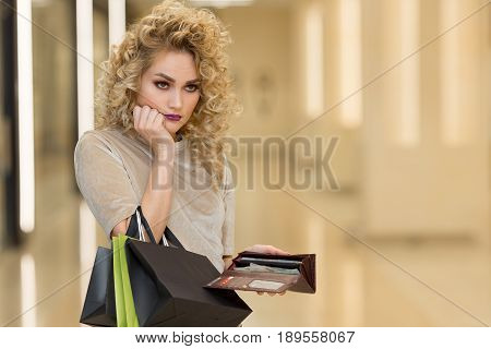 Unhappy Bankrupt Woman With Empty Wallet. Young Woman Shows Her Empty Wallet