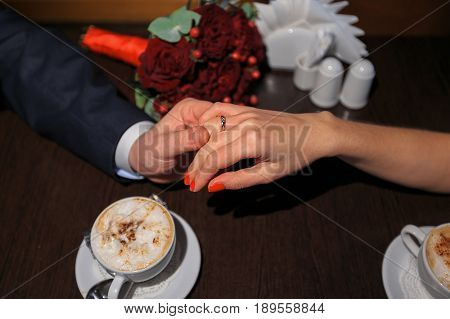 Bride And Groom Holding Each Other's Hands While Sitting At The Table