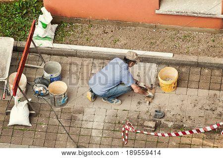Bricklayer At Work Laying Stone Blocks.
