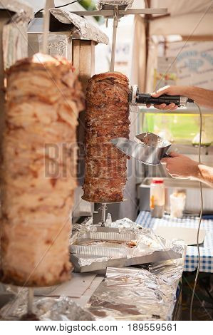 Hands Of The Cook That With Electric Knife Cut The Doner Kebab.
