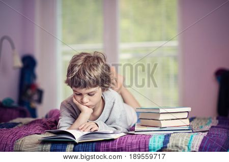 Cute little boy learning to read next to stack of books