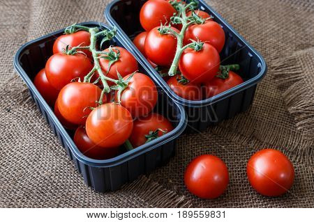 Cherry Tomatoes In A Plastic Container On Brown Background