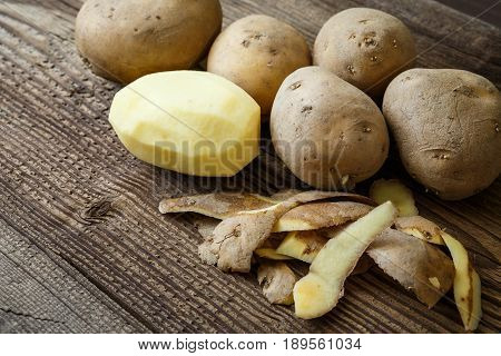 Peeled Potato And Pile Of Potatoes On Rustic Wooden Table