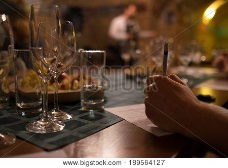 Wine tasting sommelier writes something in note table.