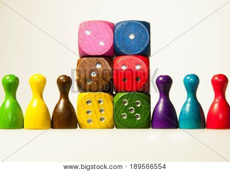 Multicolored wooden game dices with six numbers and pawns