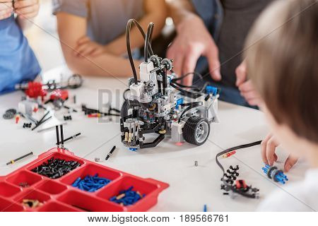 Young technicians are sitting around desk. Focus on ready made robot at countertop