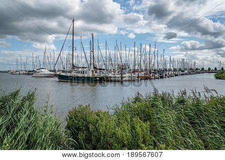 Veolendam Netherlands - August 08 2016. Ships moored in the marina of Volendam. Volendam is a popular tourist attraction in the Netherlands well known for its old fishing boats and the traditional clothing still worn by some residents