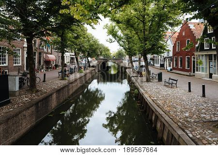 Monnickendam Netherlands - August 08 2016. Street view with old traditional houses and canal in the dutch village of Monnickendam. The town was founded by monks and it is a small fishing village today