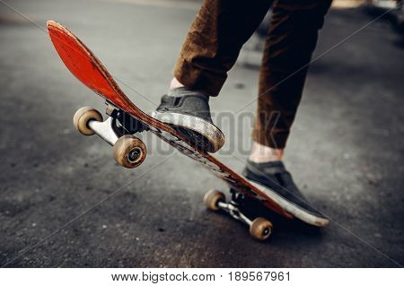 Close-up of a male guy on a skateboard doing trick kicks in shoes. The concept of doing street sports skateboarding. Monochrome and high contrast.