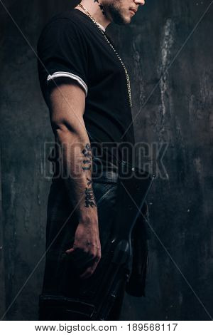Unrecognizable outlaw person with sniper rifle closeup studio shoot. Armed white gangster man with weapon on dark background. Outlaw, ghetto, murderer, robbery concept