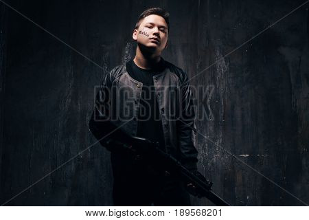 Tattooed outlaw man with sniper rifle in black cloth, studio shoot. Armed white gangster guy with weapon and tattoo on dark background. Outlaw, ghetto, murderer, robbery concept