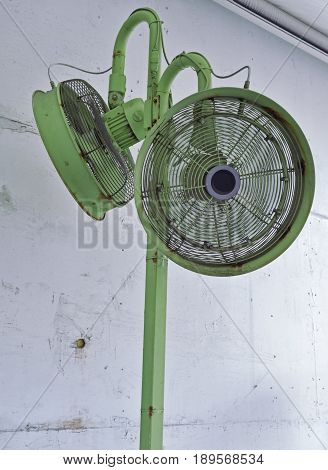 two green air fans stand against a white wall on the sidewalk of Miami Beach as they create a cooling breeze.