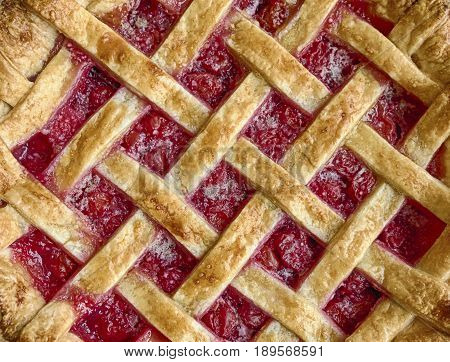 A homemade cherry pie fresh from the oven is filled with red cherry fruit and is layered with a crust made of golden dough.