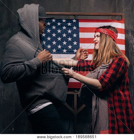 Jealousy in the US family. Conflict in couple. Angry wife and husband on USA national flag background. Divorce, social problem, home violence, youth pregnancy concept