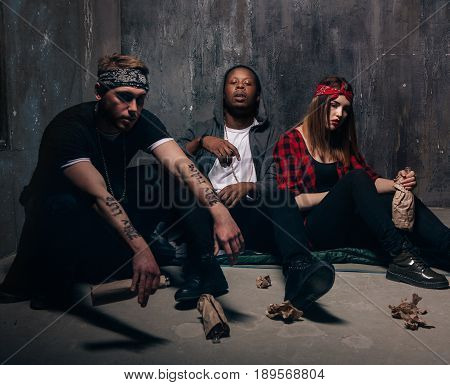 Youth group alcoholic addiction problem. Tired drunk caucasian girl holding alcohol bottle, sad and depressed guys with tattoo sits near . End of party