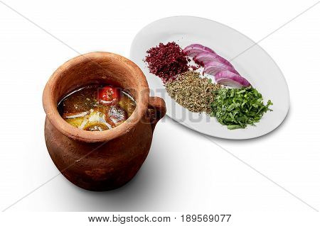 Soup in a clay pot with onions and seasonings on a white background isolation