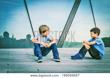 Two boys friends talking with each other outdoors