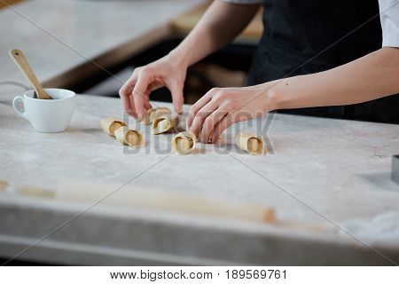 Horizontal indoors crop shot of hands of woman working with knead and forming pasta in kitchen.