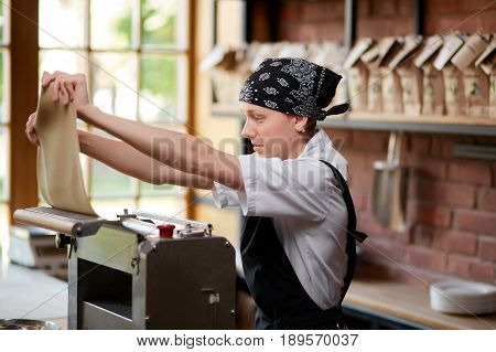 Woman working with dough and pasta rolling machine on the kitchen of restaurant. Making pasta. Making pasta in restaurant. Woman preparing knead for pasta