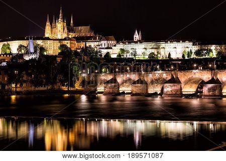 The Prague Castle and the Charles Bridge over Vltava river at night in Prague, Czech Republic.