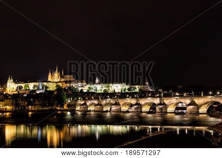 The Prague Castle and the Charles Bridge over Vltava river with nice water reflections at night in Prague, Czech Republic.