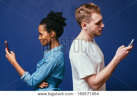 Technology separate people. Black man and white woman with phone on blue background, not talk, involved in smartphone, no attention to partner. Social network addiction, chatting, betrayal concept