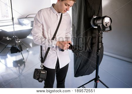 Young photographer work in studio. Man is setting photographing equipment in studio getting ready for a photo shoot