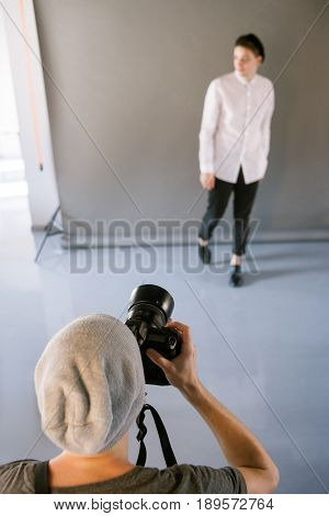Photographer and model during studio session. Unrecognizable man taking shot of male model in studio. Photo school, lookbook, fashion backstage concept
