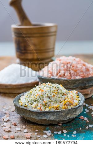 Different types of natural salt in stone bowls on wooden surface. White sea salt pink Himalayan salt Spiced salt with rosemary