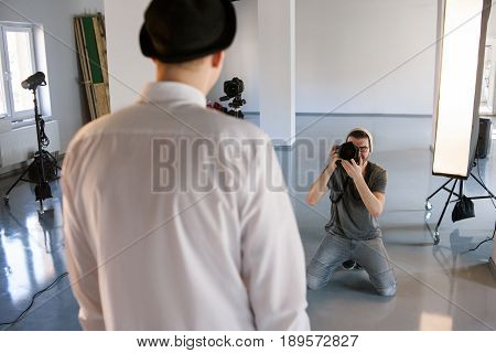 Back view of a male model posing for professional photographer in studio. POV of model during photoshooting. Fashion photo session backstage