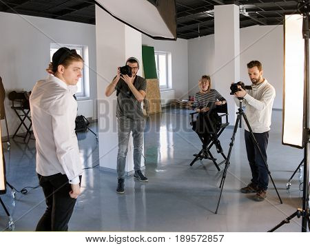 Creative team shooting in studio. Photographers taking shots of model while director observing. Fashion photo session backstage.