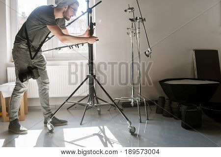 Man setting the photo tripod. Assistant work with equipment in photostudio. Professional photographer is adjusting studio for photographing.