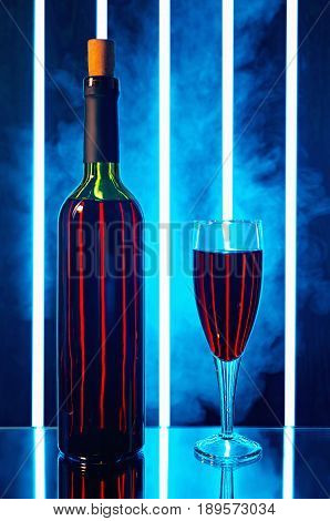 bottle of red wine in the smoke in the background is a bright vertical light strip and stand on the table mirrored