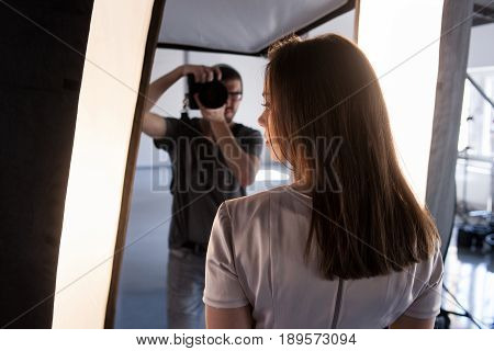 Photo session backstage. Photographer shoot model. Back view from woman's shoulder on studio interior and man, who work with camera