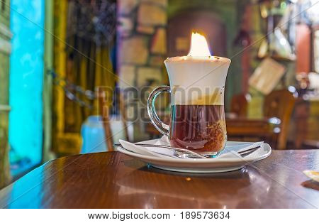LVOV UKRAINE - MAY 16 2017: The numerous cafes bars and coffee houses of old town try to attract visitors with some uniquedishes or beverages one of them offers the burning coffee on May 16 in Lvov.