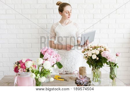 Florist check her order list before work. Business woman with notebook in flower shop. Small business management, female manager, time management, online flower sales concept