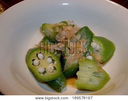 boiled okra slices on a plate Appetizer of boiled okra flavored with soy sauce served in a small white bowl