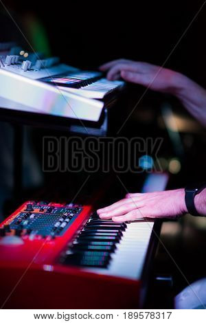 Musician playing on the double keyboard synthesizer piano keys. Musician plays a musical instrument on the concert stage