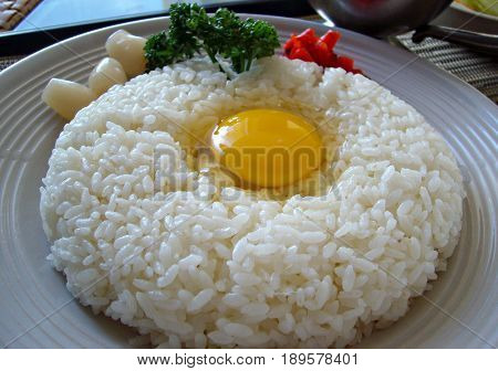 Steamed white rice with raw egg A plate of steamed white rice with a raw egg in the center, garnished with radish and herbs