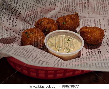 Hush puppies and creamy dipping Hush puppies from balls of cornmeal deep fried and served in a tray with creamy dipping