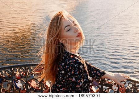 Calm woman with her eyes closed and windy hair  relaxing with her face turn toward sun