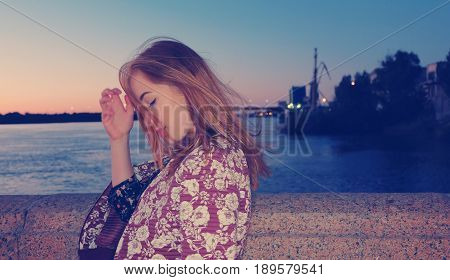 Unhappy girl posing in night alone in windy weather, vintage colorized image