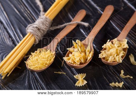 dry diferent macaroni in wooden spoon on black background
