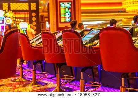 Macau, China - December 9, 2016: closeup of red armchairs and game machines inside The Venetian Casino. The Venetian Macau Casino is the famous gambling spot in Macao, the capital of casinos in Asia.