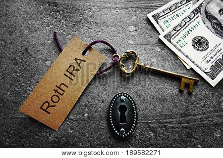 Gold key with Roth IRA tag with keyhole and cash