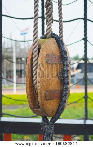ancient wooden sailboat pulley on an old restored dutch VOC ship
