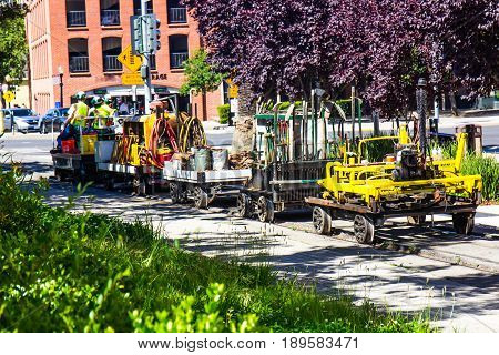 Railroad Workers Pulling Tools & Equipment On Railroad Carts